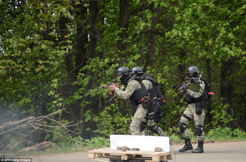 Surprise attack: Three heavily armed commandos move along a forested road near Slavyansk