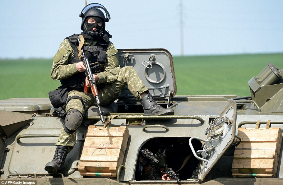 Poised: A member of the Ukrainian special forces takes position atop an armoured personnel carrier in Slovyansk