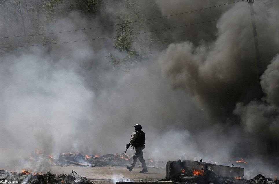 Patrol: A Ukrainian security force officer is deployed at a checkpoint set on fire and left by pro-Russian separatists