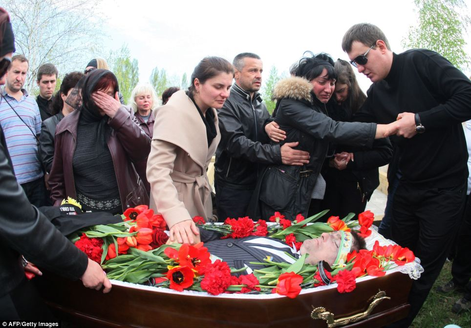 Volodymr Rybak's wife Elena breaks down in tears at the funeral of her husband
