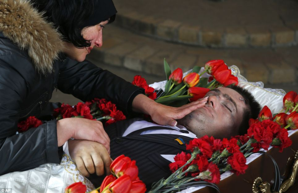 Elena, the widow of slain council man Volodymr Rybak caresses the face of her husband as his body lays in the coffin prior to his funeral