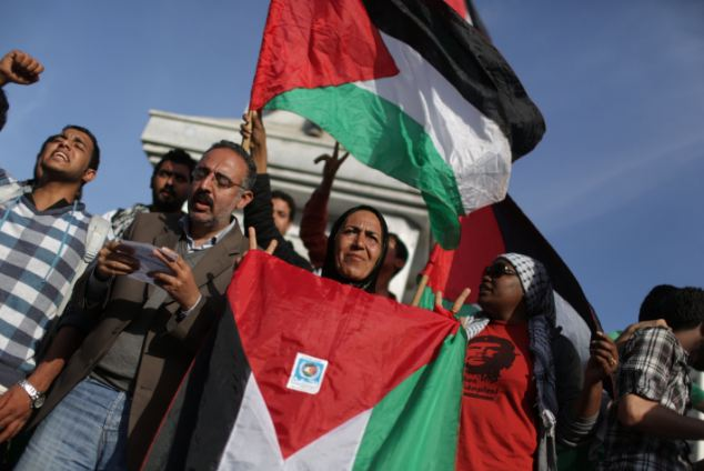 Palestinians waving Palestinian flags as they gather to celebrate the newly made reconciliation deal between Fatah and Hamas, ending a seven-year split