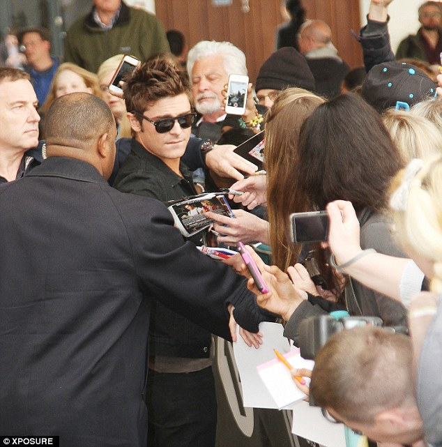 Doing his best: Zac seemed keen to sign as many pictures as he could for his waiting fans