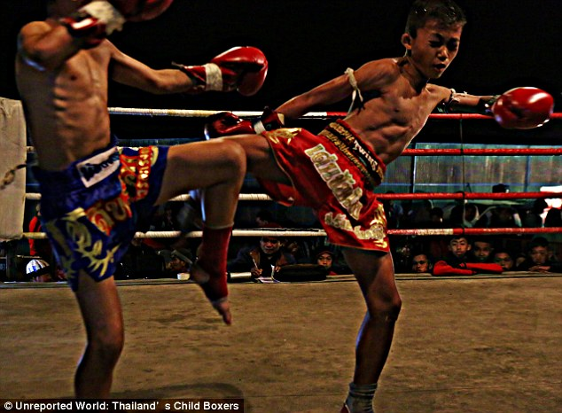 Painful: A little boy grimaces during a bout. Thai boxing allows strikes with the feet and elbows as well as fists