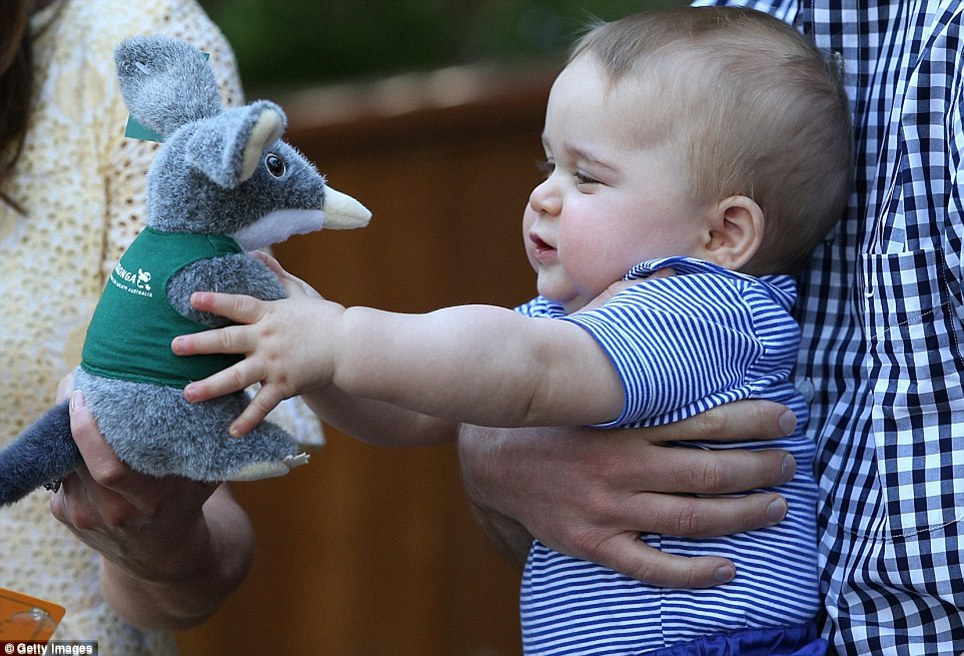 It was 'absolutely normal' for Prince George to throw his toy bilby gift to the ground which he did moments after it was presented to him (above) and is a milestone stage for children known as 'casting' which his parents should be glad their son is goign through, even if it did cause a slightly bemused Prince William to remark afterwards, 'He does love it honestly'