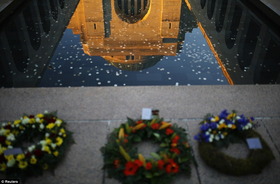 The sunlit Tomb of the Unknown Soldier is reflected in front of memorial wreaths laid out on the eve of Anzac Day at the Australian National War Memorial in Canberra