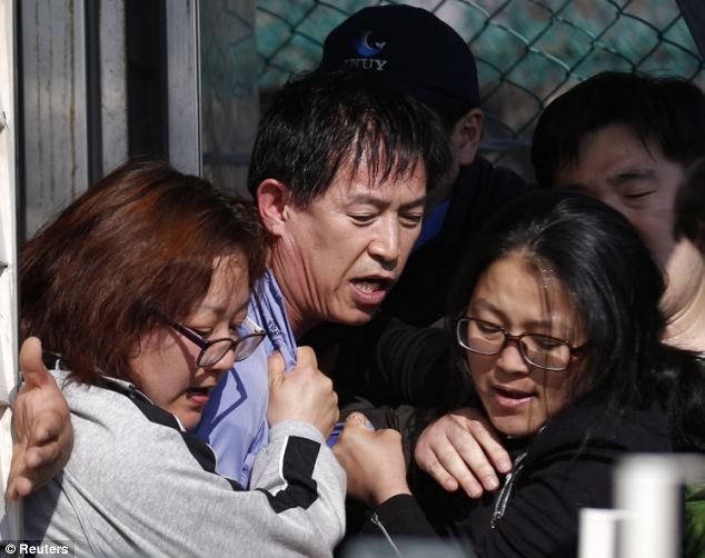 Angry family members of missing passengers onboard the capsized Sewol ferry drag Choi Sang-hwan, deputy head of the South Korean coast guard (centre, in blue), out from his office to vent their frustration at the pace of the search efforts