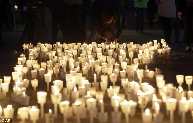 A woman places a candle with others during a candlelight vigil for the passengers of the sunken ferry Sewol in Ansan, South Korea