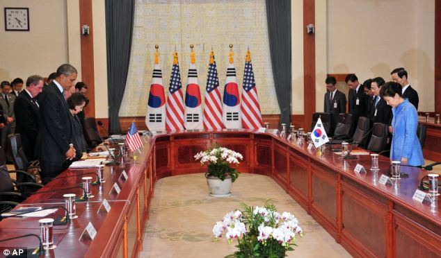 U.S. President Barack Obama, left, and South Korean President Park Geun-hye, right, pay a silent tribute to the victims of South Korea's sunken ferry Sewol during their meeting at the presidential Blue House in Seoul on Friday