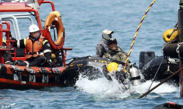 A diver jumps into the sea during the search operation for the victims of the sunken Sewol ferry