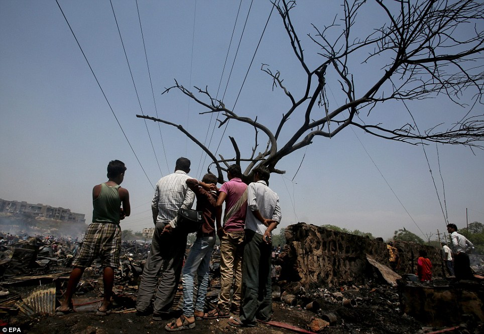 Hopeless: A group of men stand and look at the remains of 500 homes in Vasant Kunj slum in southern New Delhi. Thousands of people are thought to have been left homeless as a result of the fire