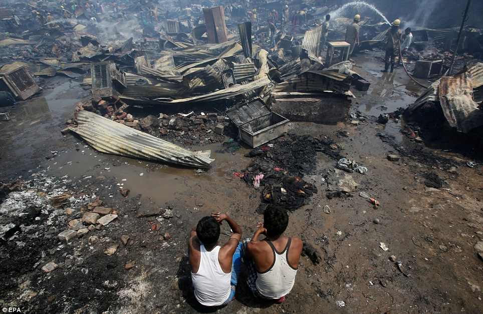 Despair: Indian men sit near the remains of their home after the fire broke out in a slum area of New Delhi. 35 fire engines and 15 ambulances attended the scene