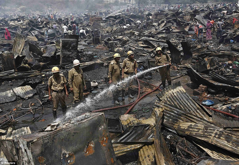 Gutted: By the time the fire was out, more than half of the thatched huts in the desperately poor neighborhood had been destroyed, leaving great piles of rubble and corrugated iron