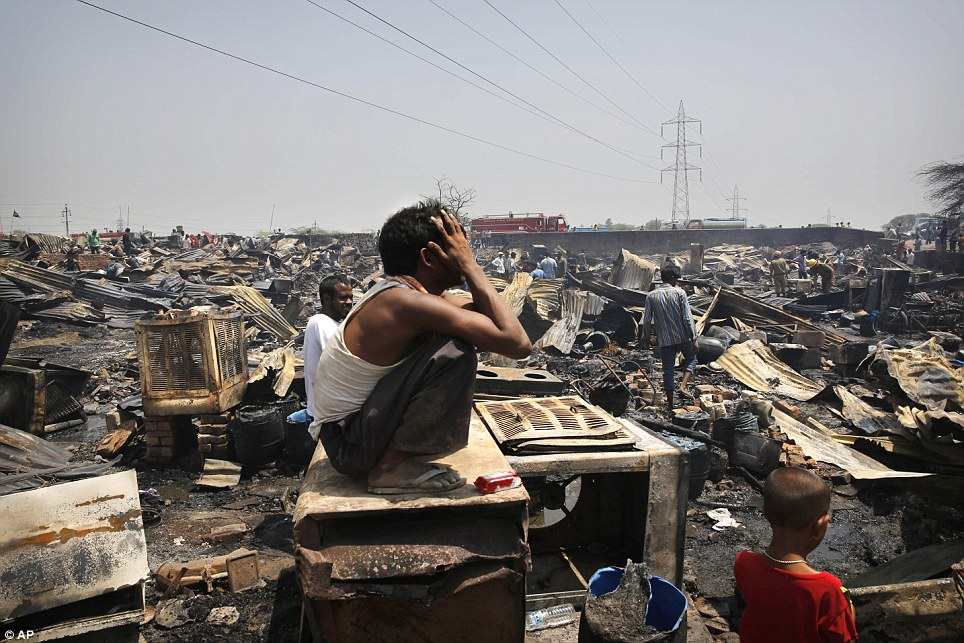 Tears: A man weeps as he sits amidst the remains of his home. Dozens of fire engines were called to the Vasant Kunj slum cluster in south New Delhi shortly after 8.30am this morning, and spent two hours battling the flames before they were finally able to get them under control