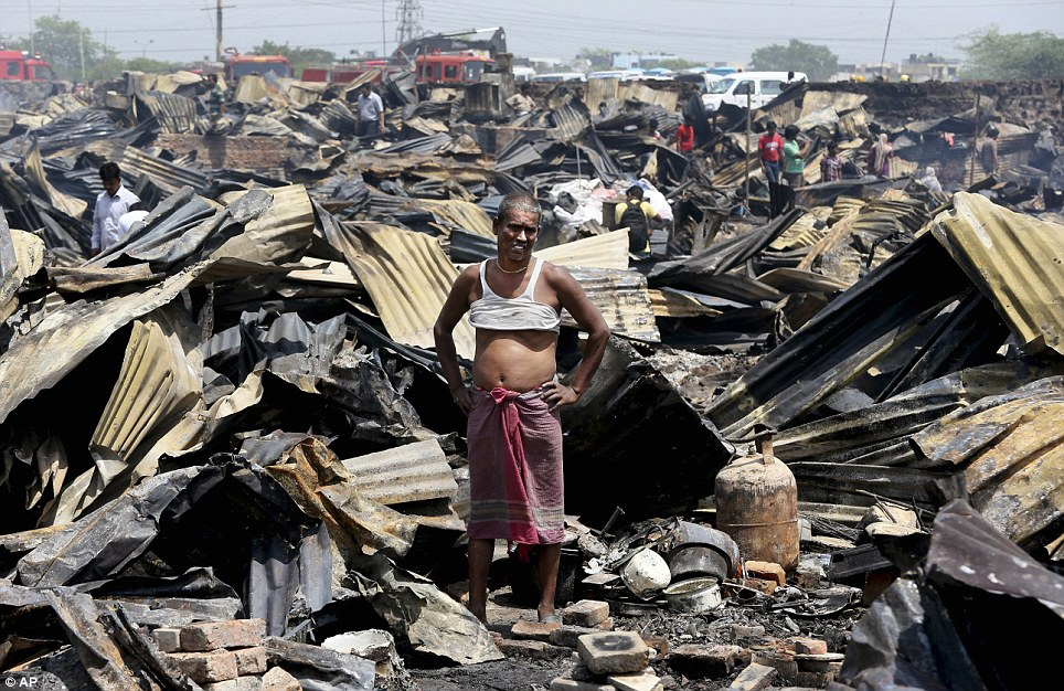 Chaos: A man stands outside his destroyed home and observes the devastation around him. Delhi's Lieutenant Governor Najeeb Jung visited the site shortly after the flames were doused and ordered the building of emergency medical camps