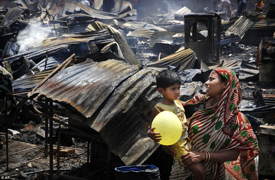 Desperate: An Indian woman holds her children outside their burnt-out home. Flames ripped through the New Delhi slum this morning, destroying nearly 500 thatched huts and leaving already impoverished families homeless
