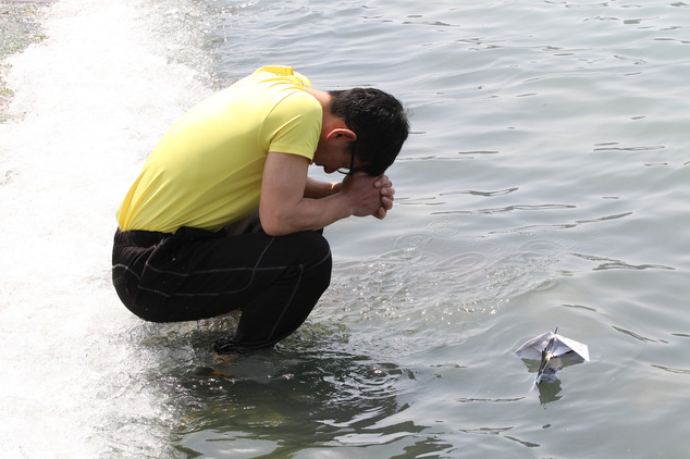 A relative of a passenger aboard the sunken ferry Sewol prays after releasing a paper boat with messages wishing for the safe return of his missing loved one