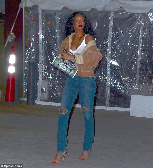 Cashing in: Rihanna toted a purse in the shape of a $1000 bill to watch the Brooklyn Nets basketball game in New York Friday