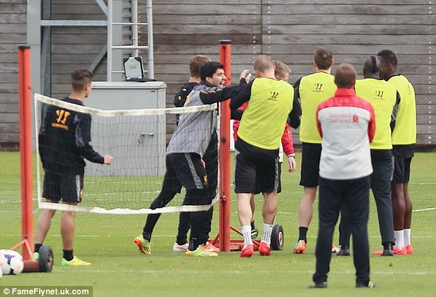 Shove: Luis Suarez pushes team-mate Martin Skrtel in a Liverpool training session on Friday