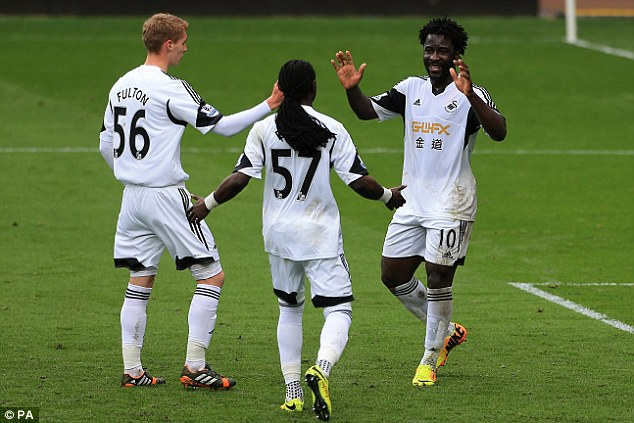Delight: Bony is congratulated by team-mates Jay Fulton and Marvin Emnes