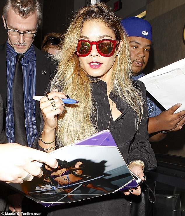 Red hot: The starlet sported slick scarlet sunglasses as she arrived in Los Angeles on Friday