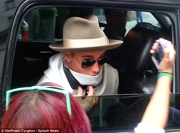 Coming out of hiding: The 20-year-old star poked his face out of his very curious outfit outside of his hotel on the same day to greet and take photos with his doting fans