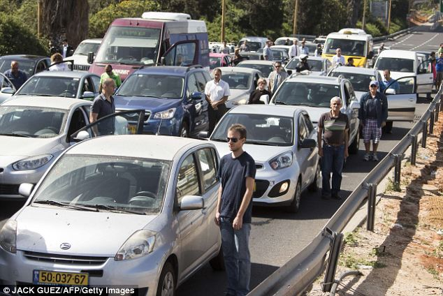 Solemn moment: Israelis stop their vehicles on the highway and stand still in the Mediterranean coastal city of Tel Aviv, as sirens sounded across Israel for a two-minute silence in memory of Holocaust victims