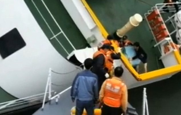 Abandon ship: Apparently wearing no trousers, Lee Joon-seok, 68, is seen clambering over the heavily-listing vessel's rails as he is helped onto a lifeboat while the ferry is still above water