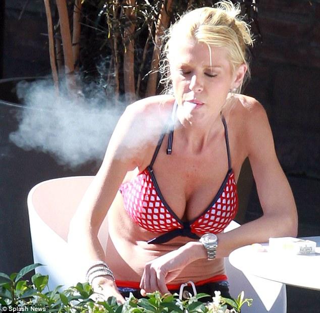 Cigarette break: Tara lit up as she enjoyed some rays by the Roosevelt pool