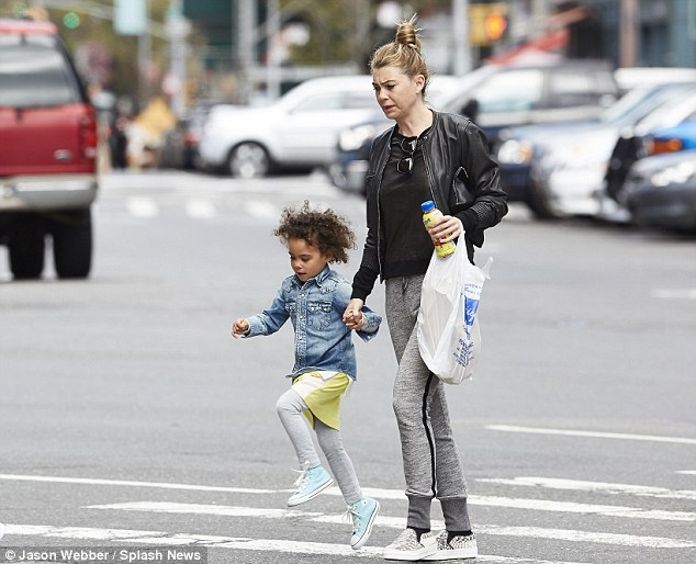 Childlike: Pompeo grasped Luna's hand, who happily skipped down the street in a pair of sky blue trainers
