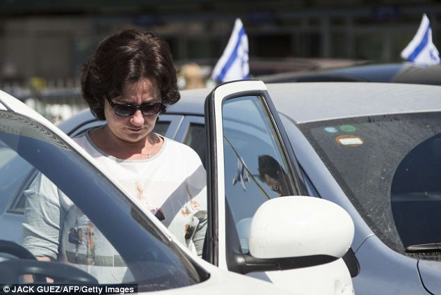 Contemplation: A woman stops her vehicle on a highway in the coastal city of Tel Aviv and stands still
