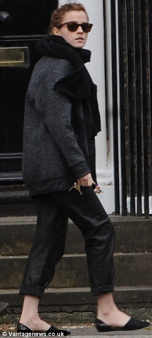 Fashionista: Emma teamed the loose leather trousers with a pair of black slip on shoes and a grey coat