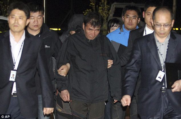 Arrest: Lee Joon-seok, centre, was pictured being led towards a court in Mokpo, south of Seoul, following his arrest