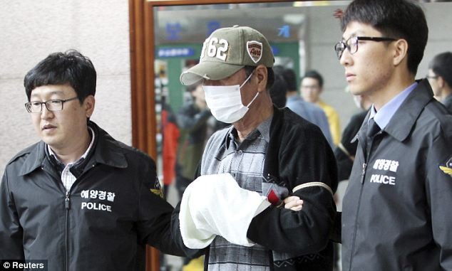 Masked and handcuffed:  Lee Joon-Seok is led to a prosecutor's office in Mokpo yesterday. Meanwhile, South Korean authorities today arrested three people on suspicion of destroying evidence connected to the sinking of the ferry