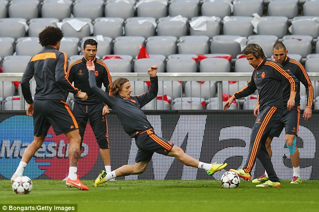 Lunging forward: Luka Modric (centre) stretches for the ball during a Real training exercise at the Allianz Arena