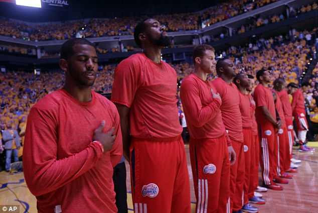 The Los Angeles Clippers players listen to the national anthem on Sunday wearing their warmup jerseys inside out to protest alleged racial remarks by team owner Donald Sterling before Game 4 of an opening-round NBA basketball playoff series against the Golden State Warriors