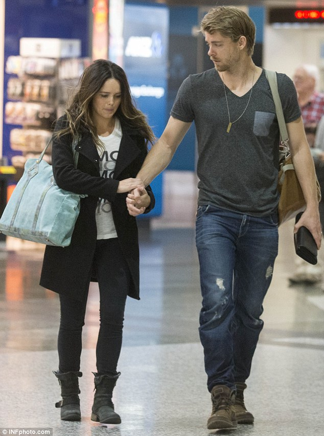 Keeping close: As the couple walked hand-in-hand, Luke couldn't keep his eyes off his wife whom he first met on the set of Home and Away