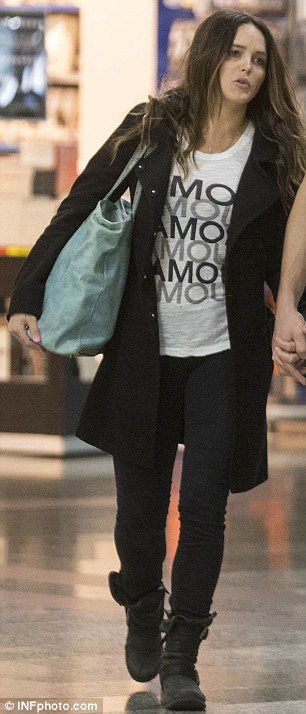 Casual chic: Rebecca opted for a white T-shirt teamed with black skinny jeans and a matching coat, contrasted with a pastel blue handbag