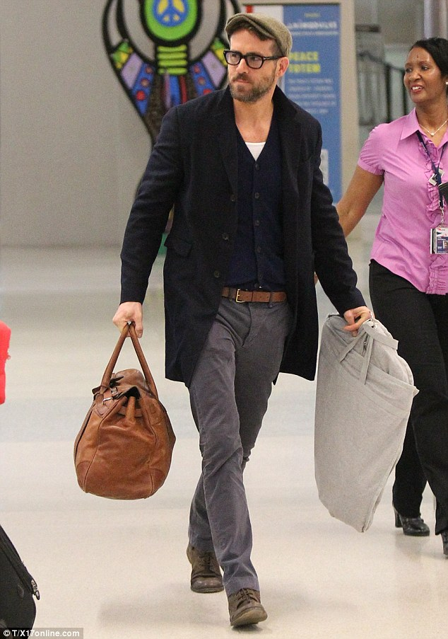 Travelling light: The 37-year-old star carried a light brown bag and some of his clothes in a protective carrier