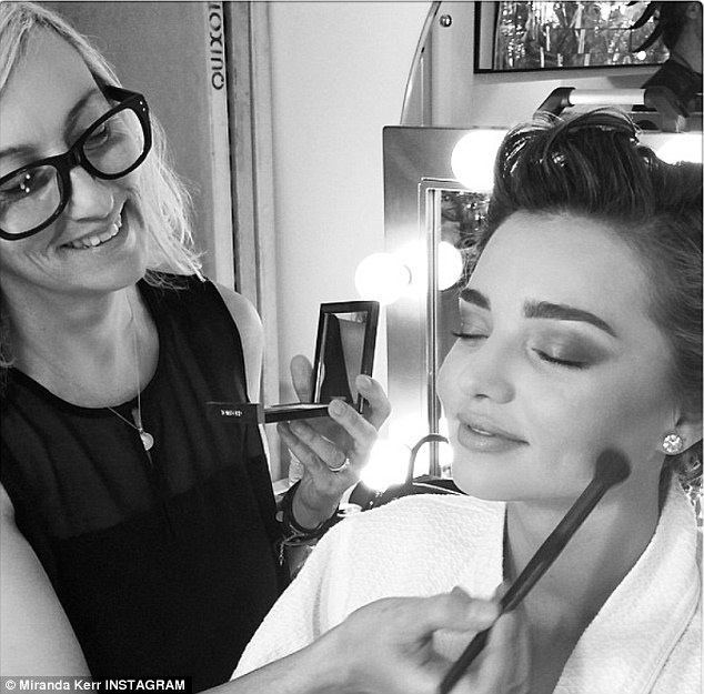 'Another day at the office!' Miranda Kerr sits pretty as she gets her make-up done for new photo shoot on Tuesday
