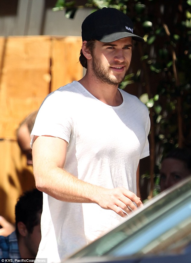 Keeping his cool: The actor was sporting more facial hair than normal and showing off his guns in a plain white t-shirt