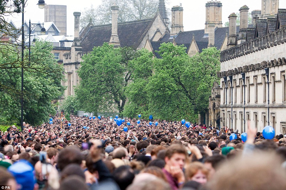 Blue balloons: People celebrate May day morning on the bridge next to Magdalen College in Oxford