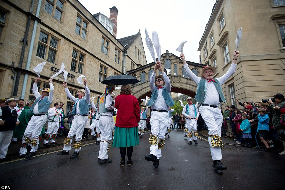 Hands in the air: Men, women and children lined the streets of Oxford this morning to watch the Morris dances take place