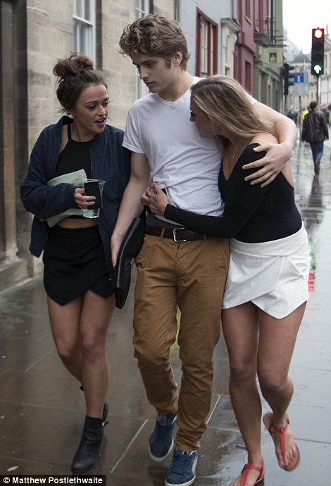 Two women walk along with a man in Oxford