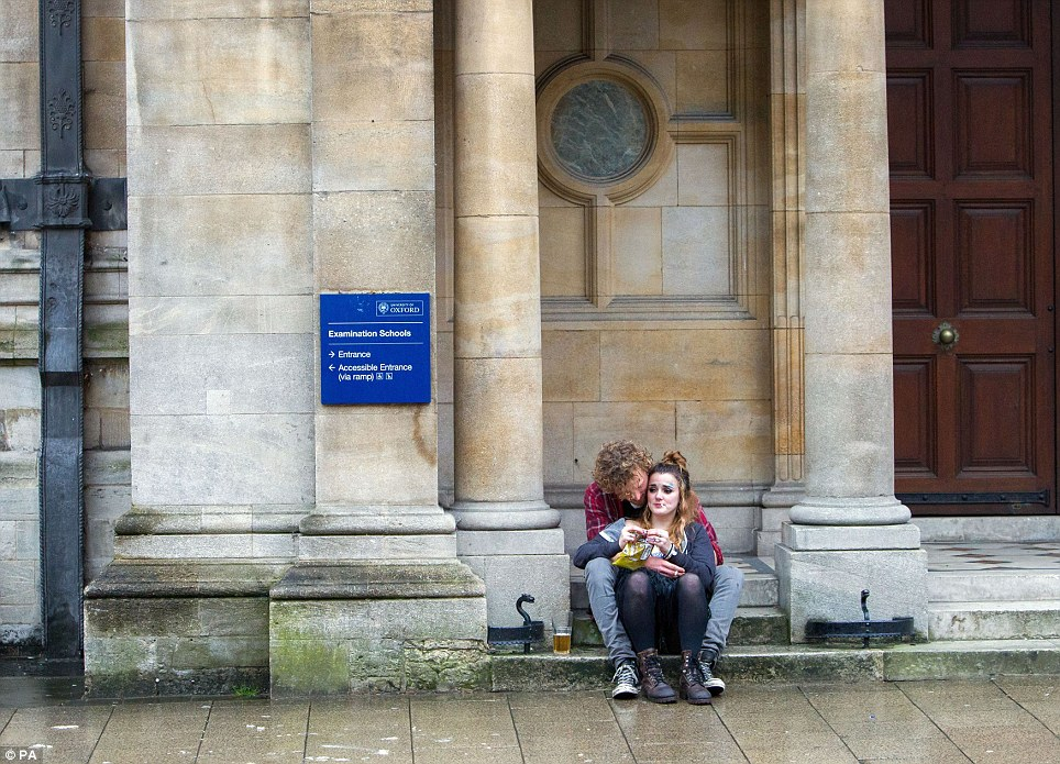 Having a rest: A man and a woman celebrate May Day morning sit down on the steps outside the University of Oxford Examination Schools