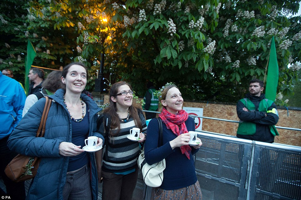 Fancy a cup of tea? Three young women smile as they attend the May Day celebrations on Magadalen Bridge in Oxford