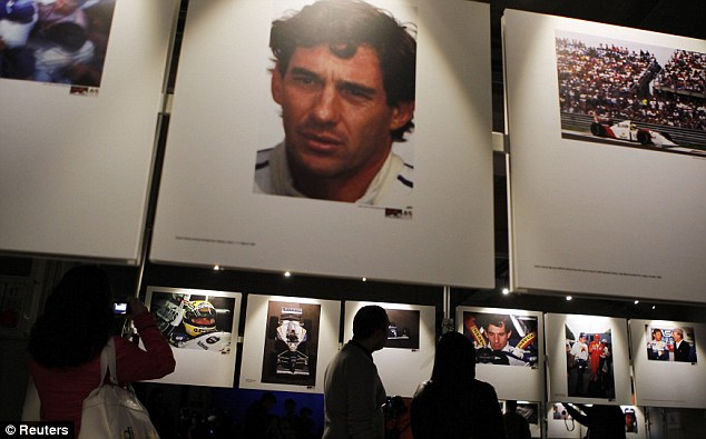 Commemoration: People look at the pictures of Brazilian Formula One driver Ayrton Senna during an exhibition at the Imola race track to mark 20 years since his death