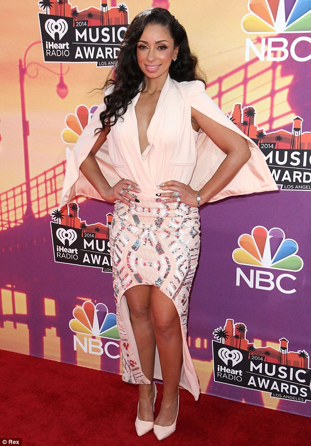 Caped crusader! Singer Mýa found a unique way to stay cool in the heat with her plunging blazer top that featured a sleeveless cape-like detail, which perfectly matched her pale pink maxi-skirt with unusual arched high-low hemline and pointy pumps