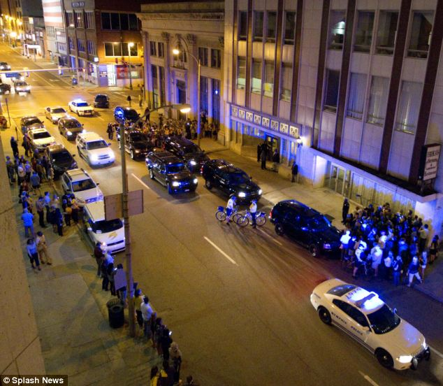 Crowds gather on the street outside the restaurant where the brothers dined last night (pictured centre right)