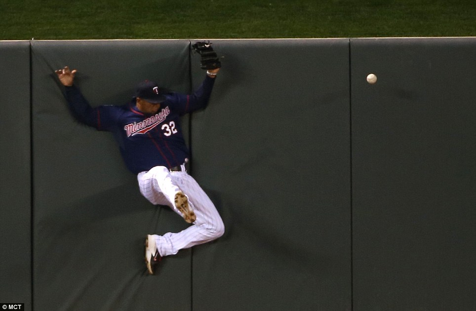 Missing out: The Minnesota Twins' Aaron Hicks slams into the wall going after missing a ball hit by the Los Angeles Dodgers' Scott Van Slyke in the sixth inning at Target Field in Minneapolis